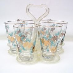 Vintage atomic glasses by David Douglas are the collectible pine cone decor turquoise glassware that are great as bar glasses or water glasses. They were made by Libbey and can be used as juice glasses. The set comes with the glass holder that is a plastic caddy with a heart shaped handle. This gorgeous set of 6 has 22 kt gold pine cone decor and turquoise pine needles. Mid century barware by Libby are elegant cocktail glasses that also look great on the dining table. These David Douglas…