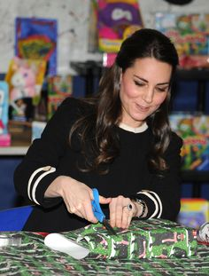Catherine, Duchess of Cambridge, helps to wrap Christmas presents during a visit with Chirlane McCray, the first lady of New York, to the Northside Center for Child Development on December 8, 2014 in New York City. The royal couple are on an official three-day visit to New York with Prince William also due to meet President Barack Obama in Washington D.C today.