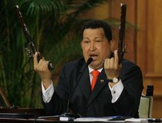 Venezuela's President Hugo Chavez holds up a pair of pistols that he says belonged to Venezuela's independence hero Simon Bolivar during a ceremony marking 229th anniversary of Bolivar's birth at Miraflores presidential palace in Caracas, Venezuela, Tuesday, July 24, 2012.  Photo: Fernando Llano / AP