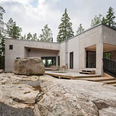 This house near Helsinki perches on a rocky bluff looking out towards the Baltic Sea and features a cranked form that shelters a decked terrace from the harsh wind.