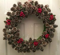 Pine cone and cherry inspired Christmas wreath. This is one of the perfect combinations when it comes to Christmas wreaths because of how the colors and the materials blend well together.