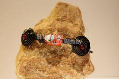 Pulsera realizada en hilo de cuero de color negro, con entrepieza central de porcelana de zapatito rojo, y motivos de alambre en color negro con abalorios en rojo.