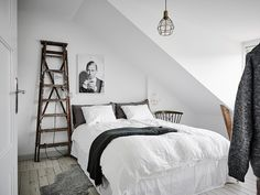 Bright and white bedroom with a rustic wooden latter and old metal lamps.
