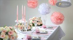 obrus biały, bieżnik, serwetki różowe i białe, girlandy wokół serwetek, pudełeczka, wizytówki, rozetki dekoracyjne mniejsze, rozetki dekoracyjne większe, podstawki szklane na talerzach, świeczniki szklane, świece proste różowe, stroiki na świece, kule bibułowe mniejsze, kule bibułowe większe