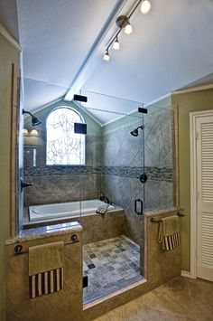 This project is pretty unique, and has been shared and repinned on various social media. There is a tub inside the shower cabin, stained glass window behind the tub, track lighting, and there is beautiful tile covering the entire shower cabin and floor. #curb #appeal #renovations