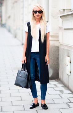 Street style look com colete longo preto, camiseta tshirt branca, calça jeans e sapato boyish preto.