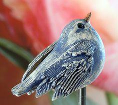 Kleiner, frei modellierter Fantasievogel naturfarben mit blauer Sruktur. Der…