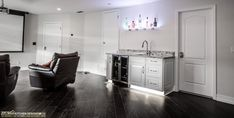 A custom designed wet bar provides functionality to this home's man cave. Visit https://www.zelmarkitchendesigns.com for more design ideas