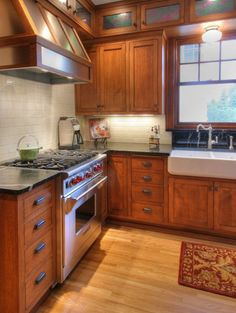 Cherry cabinets will deepen in color over time- black pulls, white sink, light floor