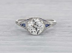 Vintage late Edwardian engagement ring made in platinum and centered with an EGL certified approximately 1.65 carat old European cut diamond with I-J color and SI1 clarity. Accented with single cut diamonds and sapphires. Circa 1920.