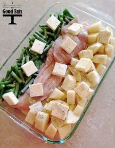 baking dish with green beans, chicken, and potatoes topped with butter and ready to be baked