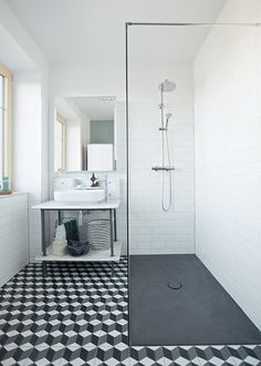 In renovating her home in Schönkirchen-Reyersdorf, Austria, Katharina Reckendorfer repurposed what she could—like a bathtub and vanity—and streamlined the rest. New black and white graphic cement tile from Mosaic del Sur, Hansgrohe fixtures, a shower plate from Bette, and Farrow & Ball's Chappell Green paint round out the room.