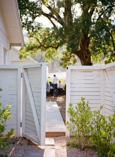 Fence boards mounted horizontally and painted glossy white create an eye-catching entrance to a private backyard space.