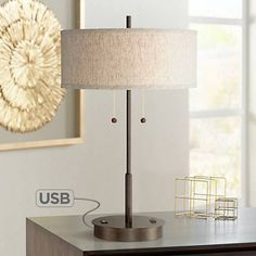 Equipped with a USB port and an outlet utility plug on its base, this slim, bronze finish transitional metal table lamp is fit for the modern era.