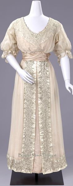 Evening dress, M.E. Verwer-Offermans, Amsterdam, 1915. Worn for a silver wedding anniversary. Light pink silk gauze over pink satin gown, trimmed with white satin edges with silver thread embroidery. Pink satin sash tied in bow in back.