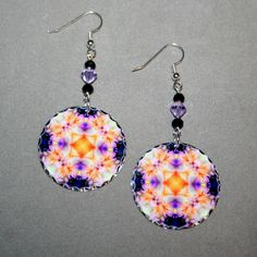 Silver dangle earrings with a Peruvian Lily mandala sacred geometry charm titled Lavender Lust. <br /> <br />These lightweight, dainty silver earrings begin with a short dangle of black Czech glass beads and lavender Swarovski crystals that accentuate the colors in the mandala charm that has scalloped edges that catch the light. The mandala charm is 1 – �...