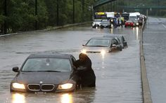 A tow truck driver floats a car out of the Don Valley Parkway Toronto floods July 2013 Posted by floodlist.com