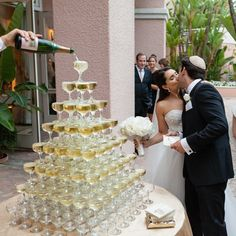 Bride & Groom Kiss by Champagne Tower | Photography: Samuel Lippke Studios. Read More:  http://www.insideweddings.com/weddings/outdoor-jewish-wedding-ceremony-glam-reception-in-beverly-hills/848/