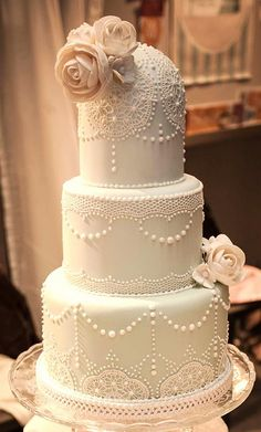Lace and pearl detail cake. Domed top with flowers look like a Roarin' 20s headpiece