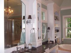 Sufficient storage space in a bathroom is always a premium, and this traditional bathroom boasts plenty of shelves for storage, as well as conveniently placed towel racks and mirrors.