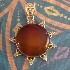 Sterling Carnelian Flower Pendant 925 It's beautiful, has a great weight to it. The points have some great patina to them. I just cleaned it in silver cleaner, and it came clean easily. A toothbrush is handy for the small detail. It is stamped 925. Jewelry