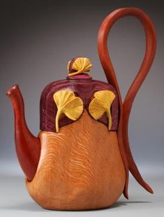 Lacewood Teapot/Purse by Denise Nielsen and George Worthington. With purpleheart handle and lid, bloodwood spout and bottom, jarra wood strap, and satinwood ginkgo leaves, 11 in. H x 9 in. L x 3.25 in. W.