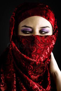 Arab young with traditional red veil, eyes intense, mystical beauty
