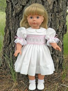 View 1 of Kaela Smocked Doll Dress for American Girl Dolls made from white batiste and smocked with pink floss and ribbons.