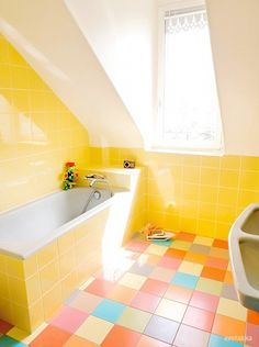 A Colourful Bathroom With A White Washstand And Mirror Yellow - Orange patterned towels for small bathroom ideas