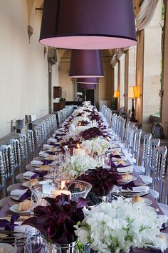 Beautiful long tables set with  purple linens and rows of burgundy mini callas and white flowers. #purple #wedding # ColinCowie Weddings