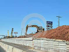 Road construction with red dirt, heavy machinery, CAT dirt moving equipment, near South Shields Plaza, Oklahoma City, Oklahoma. Busy interstate system wall and road repair. South Shields Plaza and Citi Trends signage. Cement and block wall being built.