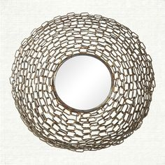 A small chain mirror by Arhaus. Like the chain mail of medieval knights, interlocking metal chains surround and enclose this mirror. The shining iro