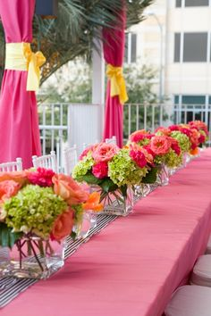 Long table with pink cloth and grosgrain ribbon. Pink + green florals. Love.