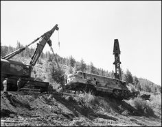 """""""NP Wrecker #45 and another wrecker rerailing NP 6701C after the June 10th, 1962 accident."""" Date: June 18, 1962 Location: Evaro, MT Photographer: Ron V. Nixon Railroad: Northern Pacific Railway Station: Evaro --- USA"""
