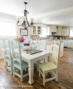country cuteness! beadboard cabinets, colored chairs & wood floor <3