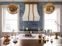 """Inspired by the blue-gray veining on the Silestone countertops, designer Matthew Quinn chose blue-gray subway tile and then warmed up the cool colors and the stainless steel appliances with brass trim. """"It's a feminine touch, like the pretty mullions on the armoires, and it balances the masculine dark woods so the kitchen appeals to everyone,"""" he says. """"People kept telling me, 'Put a bed in this room and I could live here.'"""""""