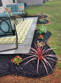 """Back patio makeover. 16"""" patio extension, plant beds with black mulch & a black retaining border (used a hose for the outline). Begonias, cordyline & hostas"""