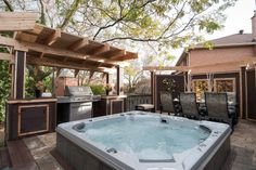 """This project's jumbo-sized hot tub is located between the dining and lounge zones, perfect to retire to after an evening meal. A stylish arched roof shelters the BBQ zone. From """"Decked Out"""" project """"The Stone Deck"""". Deck design by Paul Lafrance Design."""