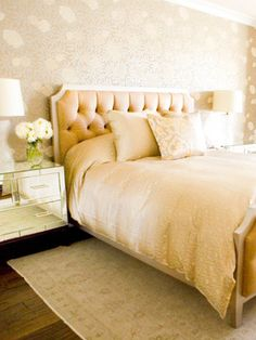 The leather-upholstered headboard and mirrored nightstands makes this bedroom ultra-glamorous