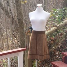 """SALE! LOUIS VUITTON Suede Skirt W/Crochet Accts This one-of-a-kind piece from a design house renown for the utmost in quality & sophistication possesses both elegance as well as its own unparalleled, yet nostalgic, vintage feel.  * 100% genuine lambskin; * Lining is 100% silk; * Ultra soft, camel-hued, suede envelopes the waist in an a-line design; * Crochet pattern forms unique waistband in contrasting, dark stitch; * Coordinating, crochet stitch throughout; * 7.5"""" slits on either side…"""