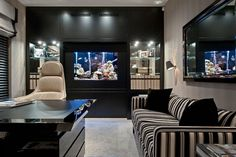 glamourous + somewhere to put lukes fishtank Study by Hill House Interiors. Bespoke sofa covered in black ivory and taupe fabric and a black lacquer and printed leather partners' desk by Turri.