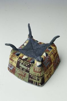 Ceremonial Hat  culture: Wari  date: 8th-10th century  medium: Alpaca; knotted, with supplementary pile  dimensions: 3 1/2 x 5 x 5 in. (8.89 x 12.7 x 12.7 cm)  location: South America, Peru, Central Coast region  gallery note: We know from ceramic effigy figures that four-corner hats such as this one appear to be linked with warriors and with ceremonies that were perhaps associated with warfare. It is possible that the four corner peaks may be a reference to the ears of animals worn as headd