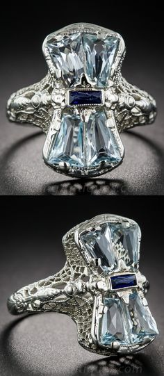 Double Aquamarine Art Deco Ring,  Actually, if you take a closer look, this is a quadruple aquamarine ring! Four perfectly matched, faceted, tapered baguette-shape gemstones, exhibiting a refreshing pastel blue hue, are arrayed in a mirror-image formation, interrupted by a scissor-cut, horizontally set sapphire (synthetic). A fanciful filigree mounting, die-struck in 14K white gold, circa 1930s, provides the setting.
