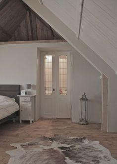 Mooie #landelijke #slaapkamer in een hoge ruimte met #puntdak. Mooie #houten #wanden, houten #vloer, mooie #oude #deur en #koeienhuid #kleed. #bedroom #rustic #wood #white #cow
