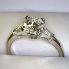 One classic platinum and diamond engagement ring. This ring consists of a .93 round brilliant diamond. This diamond has been set into a heavy four prong basket mounting. Flanking this center stone are (2) tapered baguette diamonds, one each side and have been secured by bar settings.