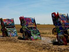 """Route 66 Road Trip: Here's What You Need To See Cadillac Ranch a public art project and sculpture is located in Amarillo, Texas and is a breathtaking look at, among other things, the evolution of mid-20th century Cadillacs that lie half-burned in the ground.    Visitors are allowed to contribute to the art piece by painting on the vehicles, which were immortalized in Bruce Springsteen's """"Cadillac Ranch,"""" a macabre story of death and dying told through this Route 66 landmark."""