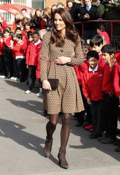 Kate Middleton–Duchess Catherine–visited the Rose Hill School in Oxford today, wearing head-to-toe brown. The dress/coat is by Orla Kiely, the ankle boots by Aquatalia.
