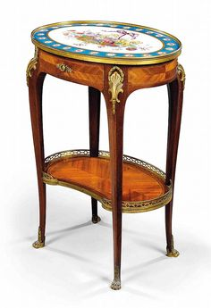 A FRENCH ORMOLU AND SEVRES STYLE TURQUOISE GROUND PORCELAIN-MOUNTED MAHOGANY AND AMARANTH TABLE EN CHIFFONIERE<br />BY PAUL SORMANI, PARIS, LAST QUARTER 19TH CENTURY <br />The slightly galleried oval top inset with a plaque painted to the centre with a ribbon-suspended wicker basket laden with summer flowers, the turquoise ground border with gilt roundels decorated with rose buds and blooms, above a line-inlaid quarter-veneered frieze with single drawer to the front, on shaped tapering ...