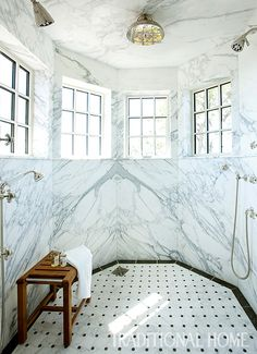 This spacious, octagonal shower has Calacatta Gold marble walls and a custom mosaic tile floor. - Photo: Erica Dines / Design: Tammy Connor