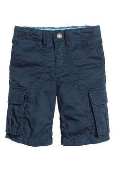 Short cargo: Short en coton lavé. Modèle avec poches latérales et poches à rabat pressionné sur les jambes et dans le dos. Élastique réglable à la taille et braguette avec fermeture à glissière et bouton-pression.